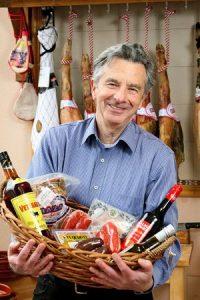 Dr. Jorge Paredes-Gebhard mit einem Geschenkkorb im Verkaufsraum des Spezialitätenladens Bodegas Andaluzas in Gostenhof in Nürnberg. Foto: Mile Cindric