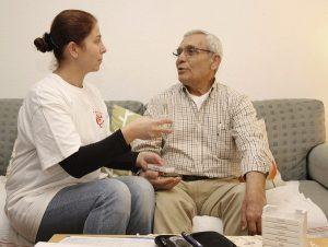 Die Alten- und Krankenpflegerin Aysena Gülec vom Ambulanten Dienst Rosenau übergibt Patient Mustafa Tasbolat Medikamente. In Nürnberg leben rund 15.500 Senioren mit Migrationshintergrund. Foto: epd